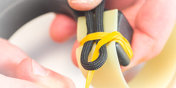 6. Carefully holding the tensioned wraps in place, feed the tag end through the loop.